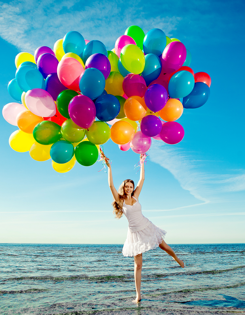 Beauty young stylish woman with multi-colored rainbow balloons in hands against the sky. Positive girl on nature. Smiling woman outdoors enjoying.